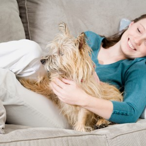 Woman relaxing on couch with pet dog